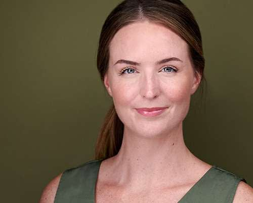 Professional headshot of a women against a green background